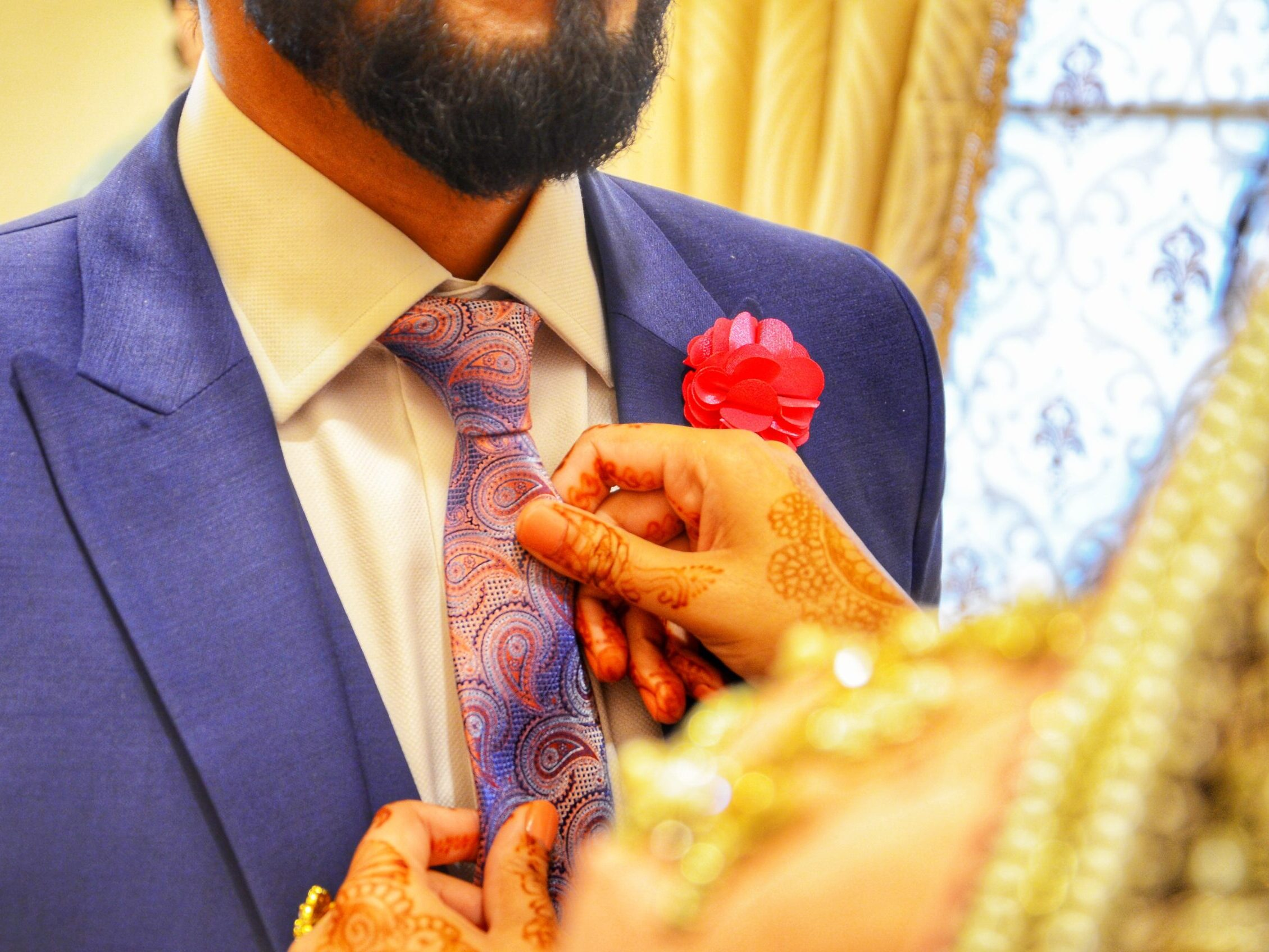 person fixing necktie of another man