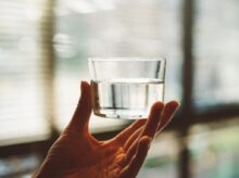 person holding clear glass cup with half-filled water