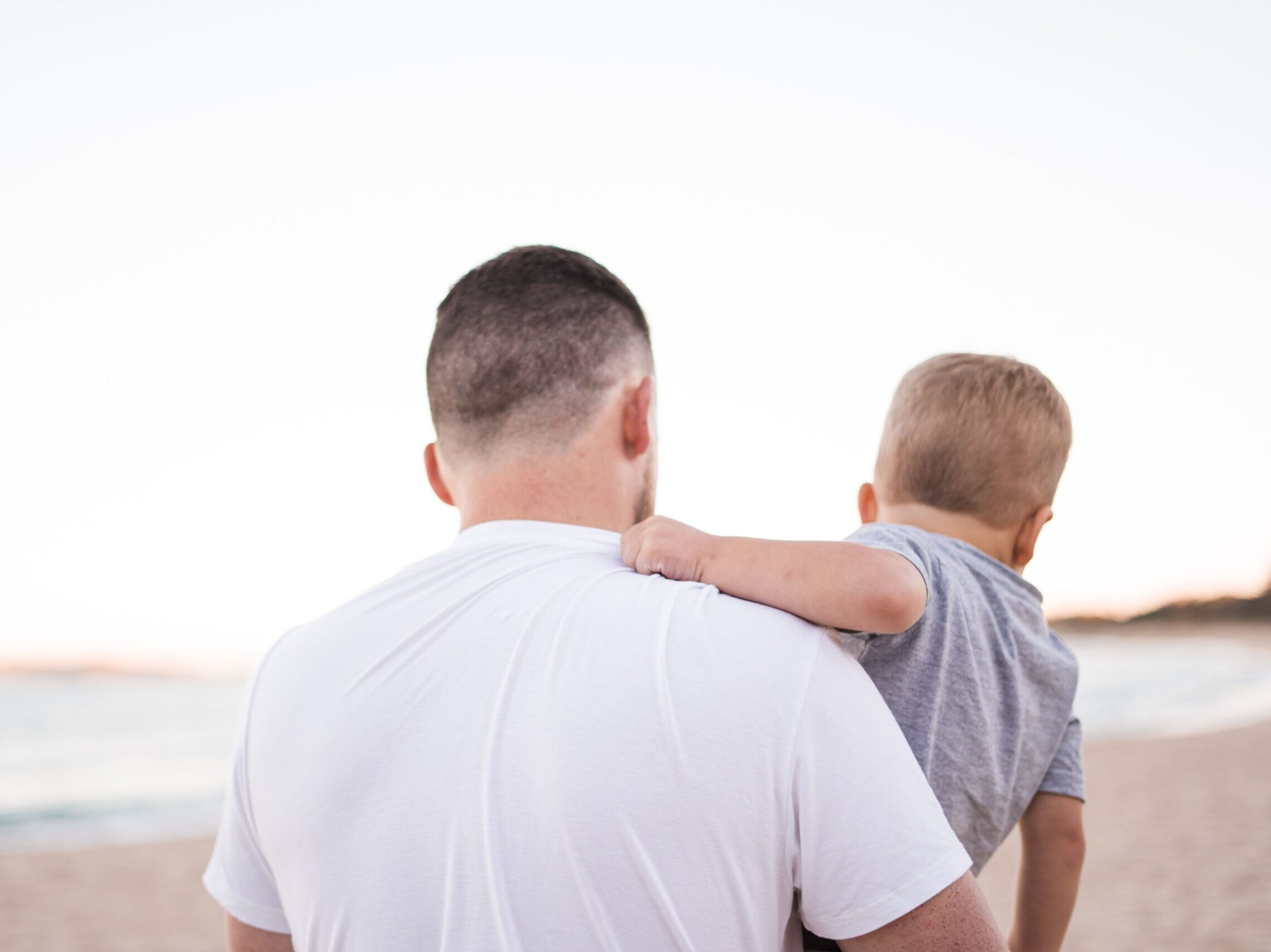man carrying baby near the ocean