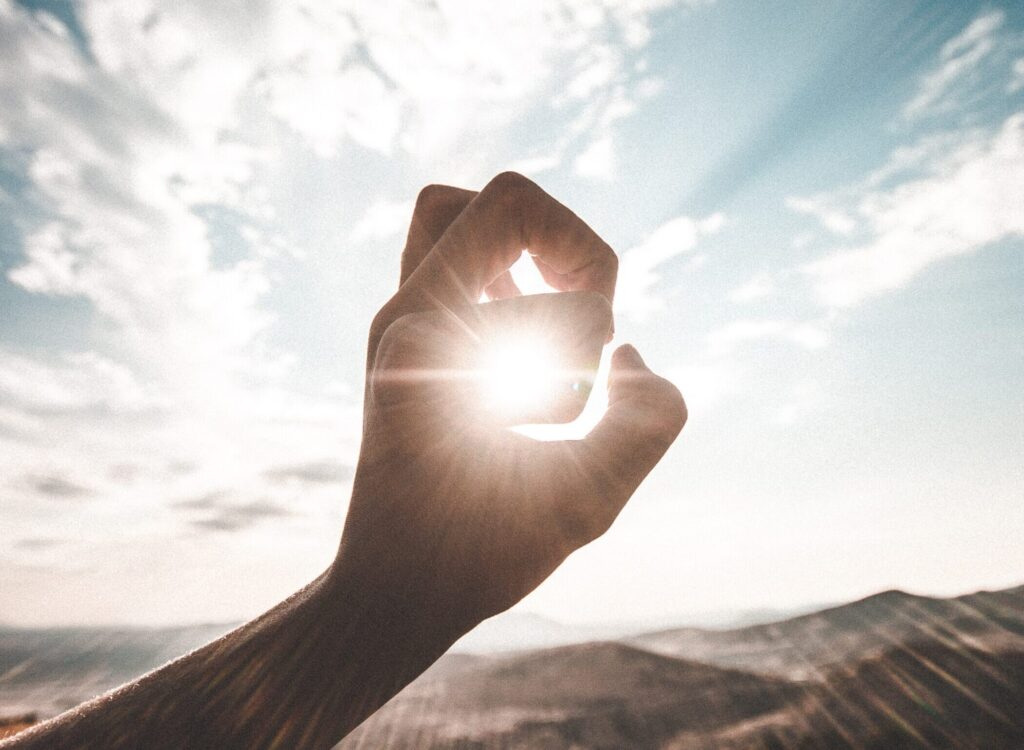 photography of sun glaring through the hole of finger