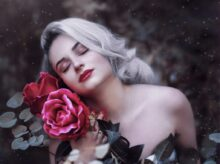 selective focus photography of woman beside rose flower