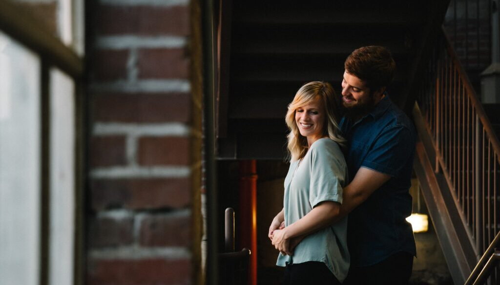 man hugging woman from behind near stair