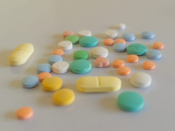 white yellow and teal medication pill