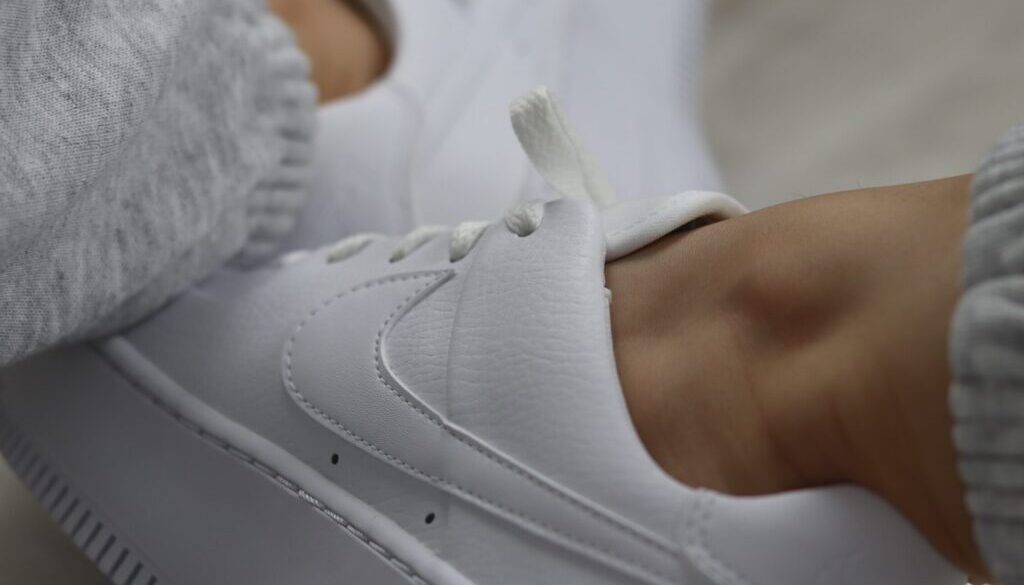 person wearing white nike athletic shoes