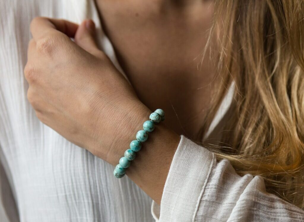woman in white long sleeve shirt wearing silver and green beaded bracelet