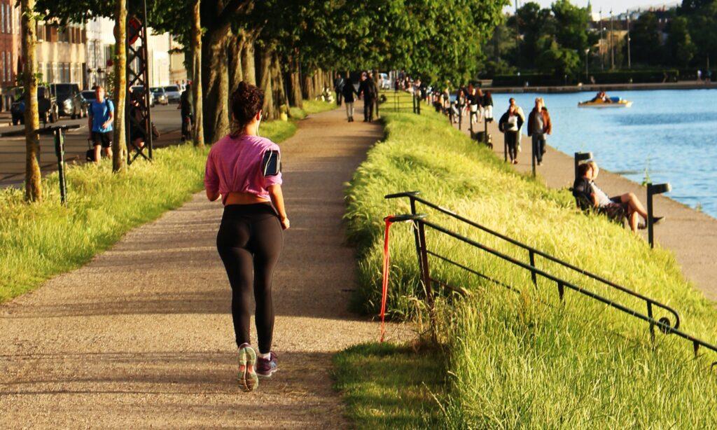 woman jogging near body of water