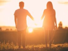 man and woman holding hands white facing sunset